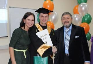 Выпускник школы держит диплом стоя рядом с преподавателями